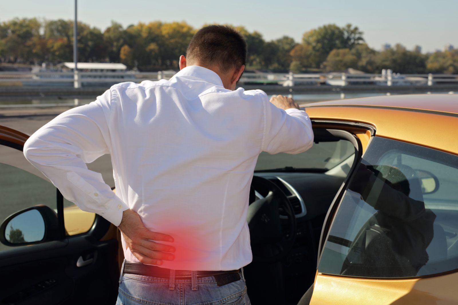 Man Holding Lower Back Outside of Car