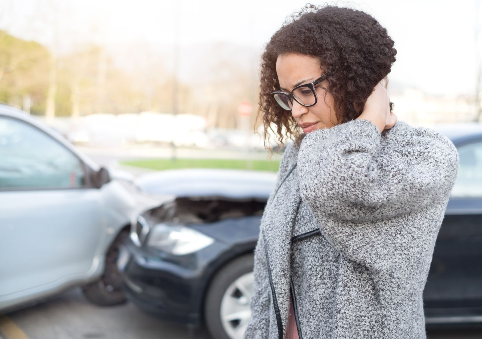 Woman Holding Neck Next to Cars After Accident