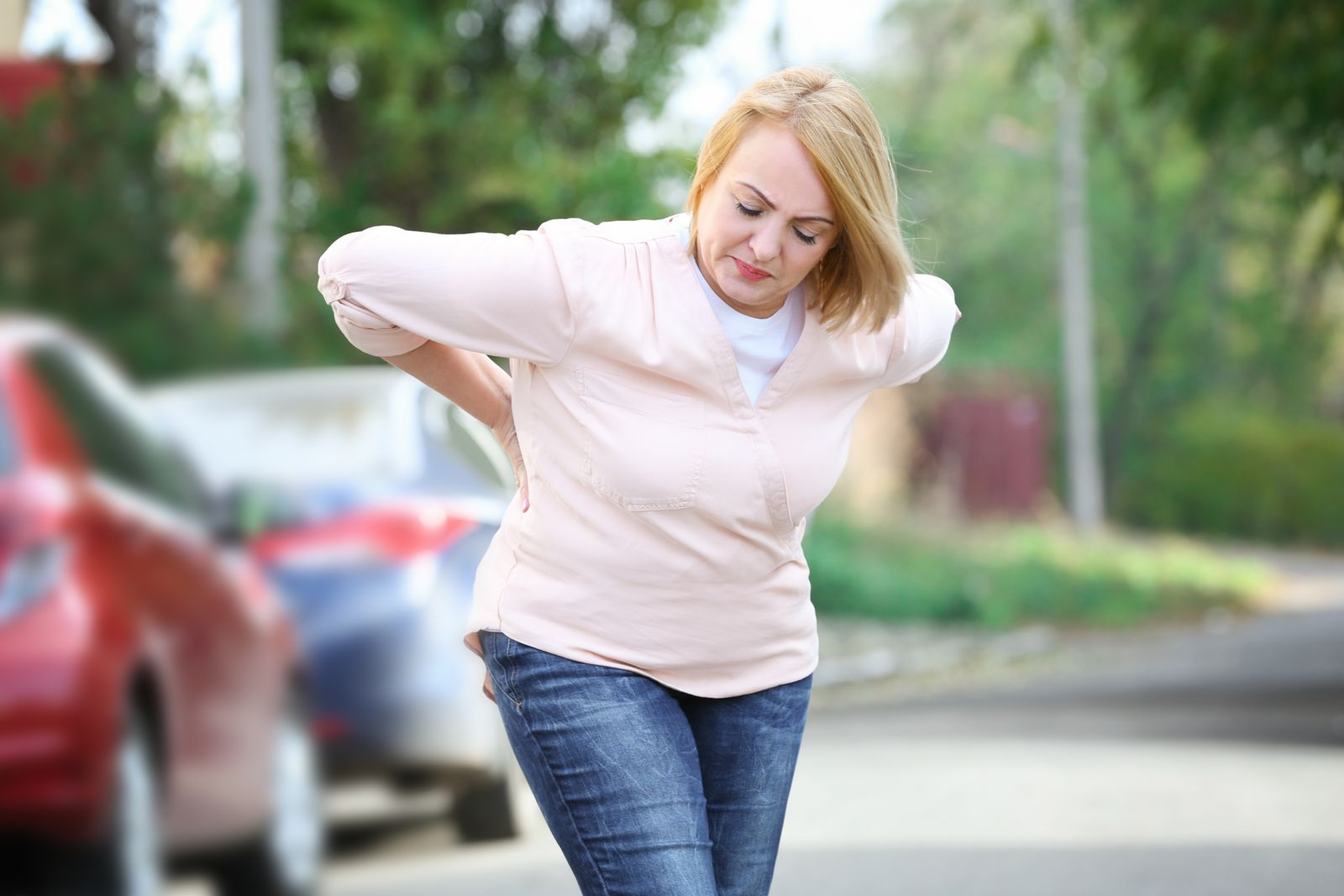 Woman With Backache Walking Away from Cars