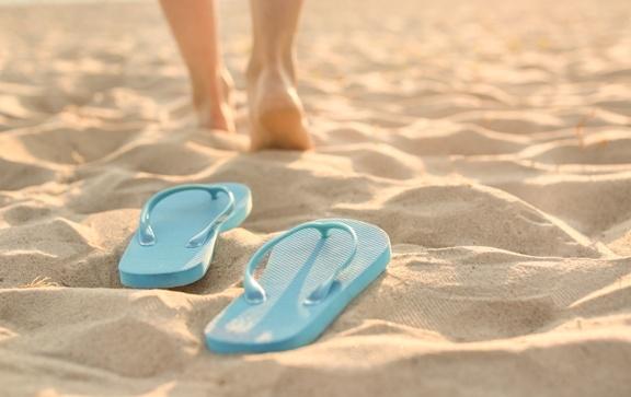 walking away from flip flops on the beach