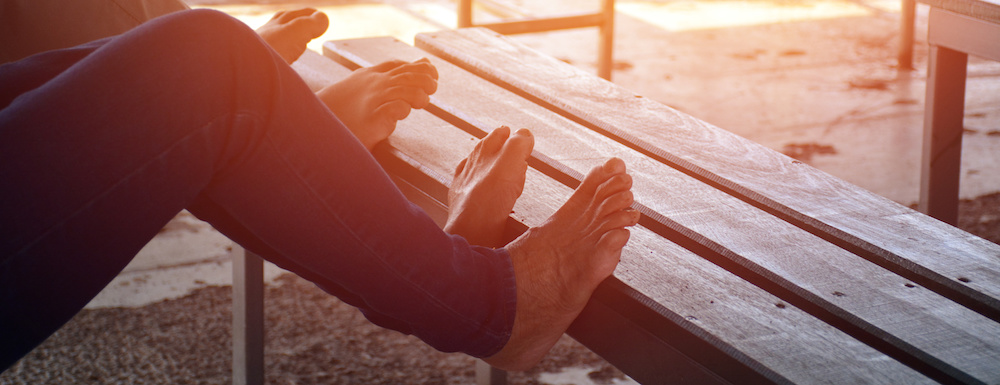 Two people with their feet up and arched over a bench