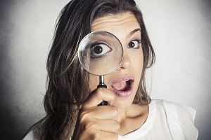 Woman's eye peers through a magnifying lens