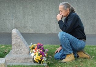 Man Mourning the Loss of a Family Member at a Grave