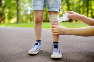child with knee injury getting medical bandage