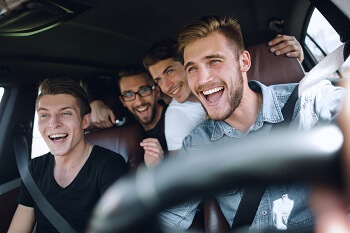 Group of friends riding in car as passengers