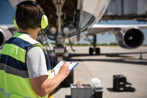 airline maintenance worker inspecting airplane