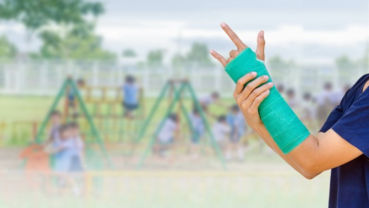 child with broken arm in front of playground equipment