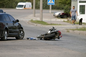 damaged motorcycle in street after car accident