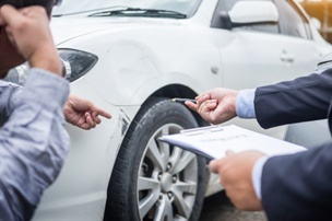 insurance adjuster inspecting car accident damage