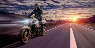 motorcycle rider on street at sunset