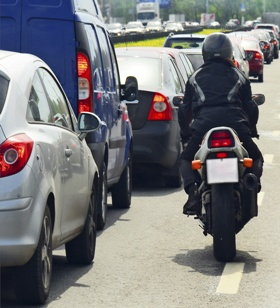 motorcycle rider in traffic sharing lane with cars