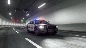 police car driving through highway tunnel