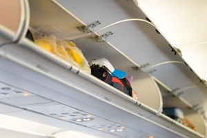 open overhead luggage bin on airplane