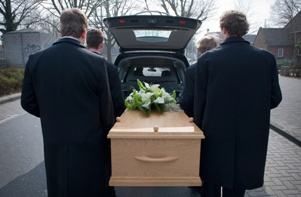 pallbearers putting casket in hearse at funeral