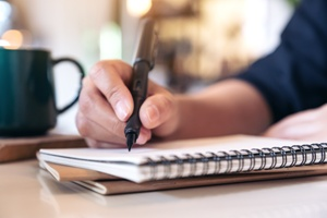 person taking notes in notebook next to coffee mug