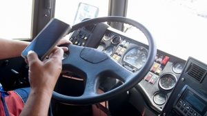 semi truck driving using cell phone at the wheel