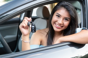 happy teen driver in car showing car keys