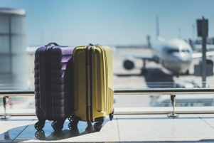 suitcases in airport with airplane in background