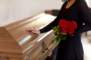 woman holding flowers with hand on coffin at funeral