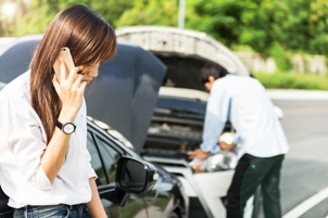 woman making cellphone call head on collision in background