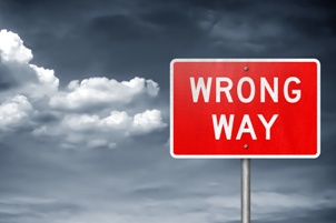 wrong way road sign with cloudy sky background