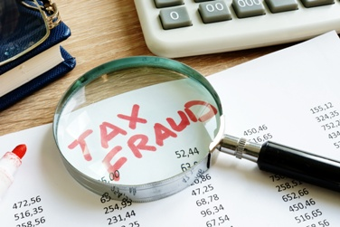 Tax Fraud Paperwork With a Magnifying Glass Miami Federal Crimes Lawyer