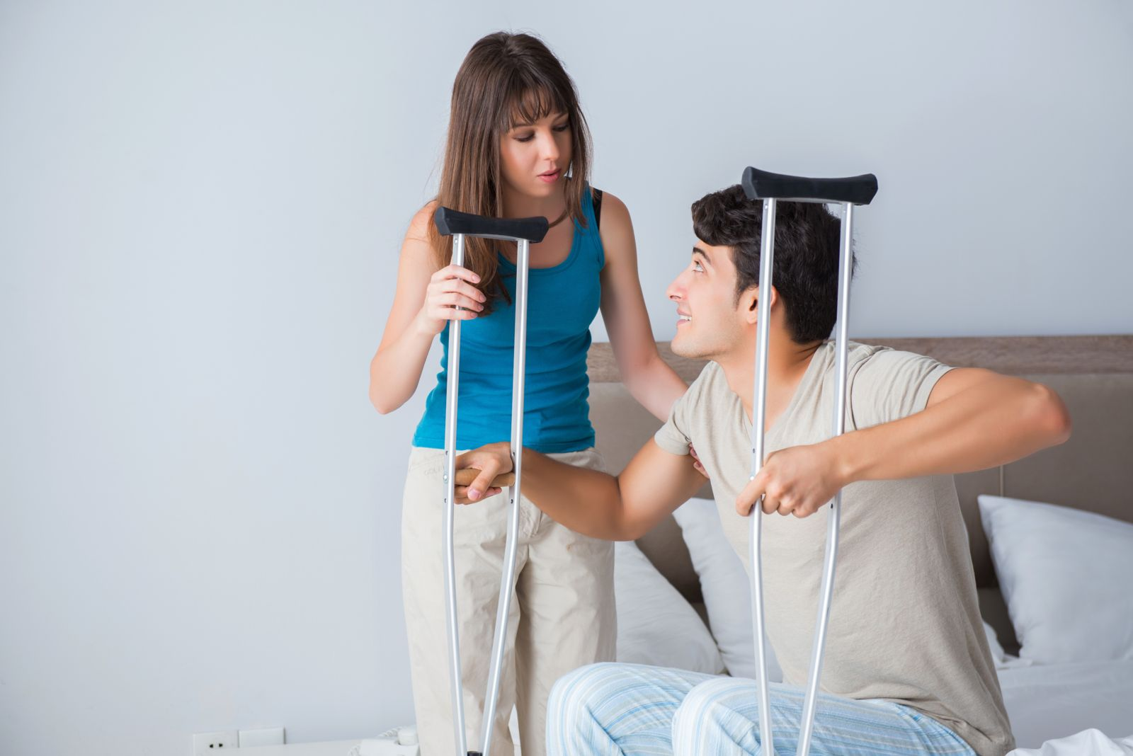 woman helping man with crutches