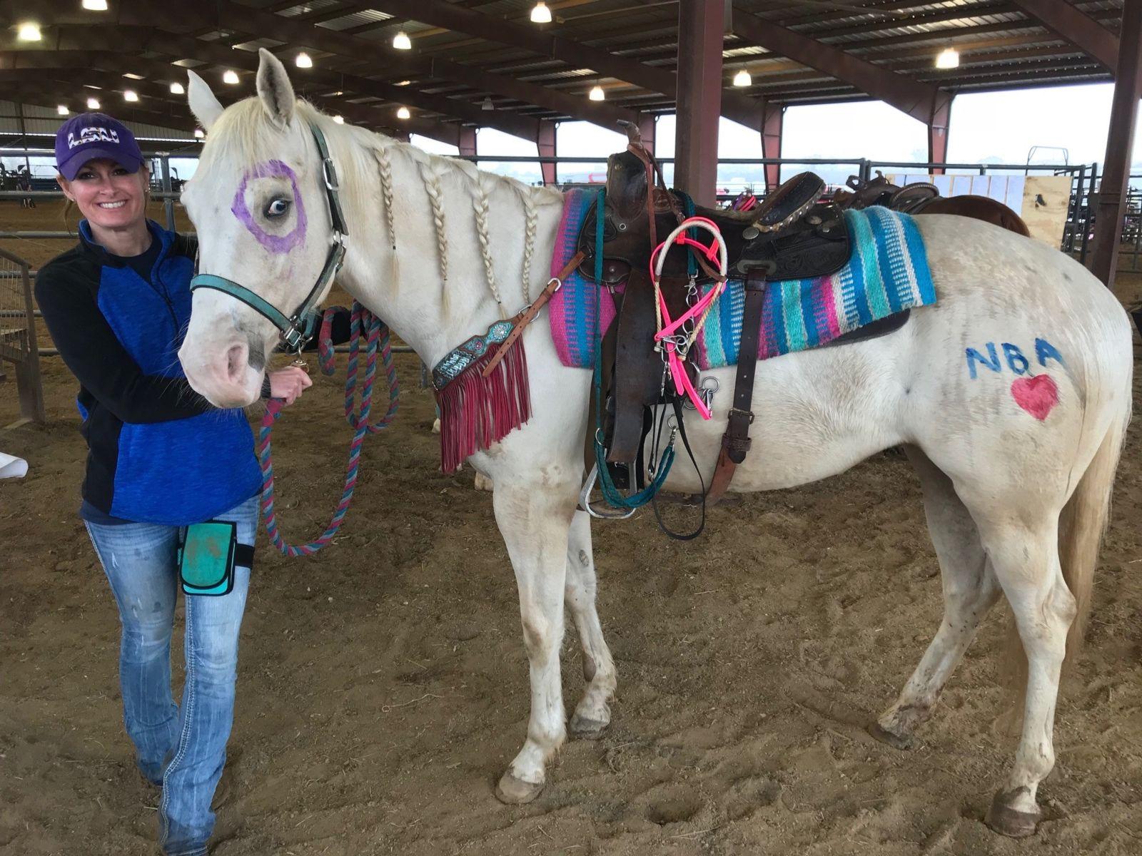 Lauren shows off her horse Blue's colorful finger paint.