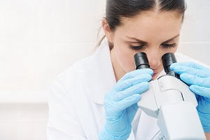 A young researcher examines cancer cells with a medical microscope