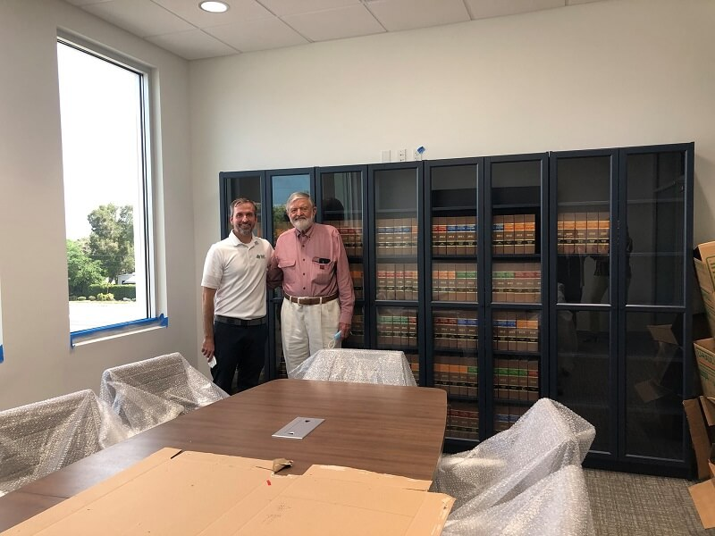 Rep and Dennis DeLoach in front of the new bookshelves