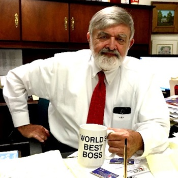 Dennis R. DeLoach Jr. at his desk holding his best boss coffee cup