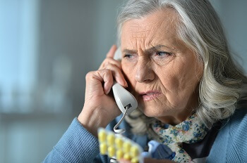 Elderly woman on the phone at risk of exploitation