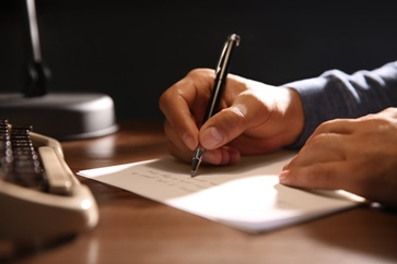 Man Writing a Notice of Administration Draft