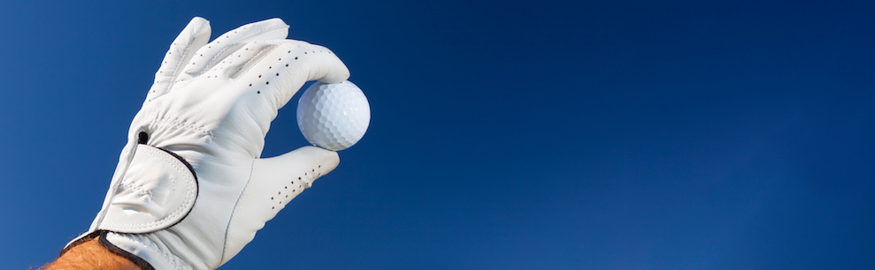 Man holding up a golf ball in the air