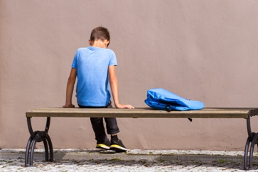 Child Sitting on a Bench With a Backpack