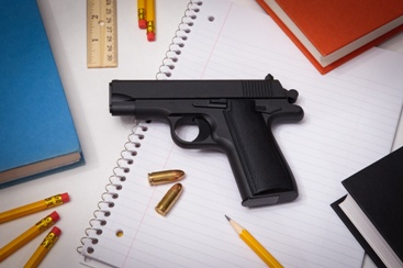 Gun Sitting on Top of School Supplies