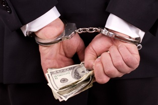 Businessman in Handcuffs Holding Money After Committing a White Collar Crime
