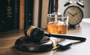 Car Keys and a Glass of Alcohol With a Wooden Gavel