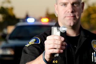 Police Officer Holding a Breathalyzer in His Hand