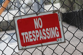 Red trespassing sign on Virginia property fence