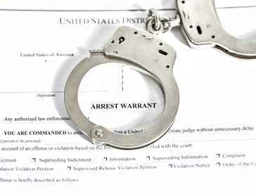 Arrest Warrant Paperwork and Handcuffs