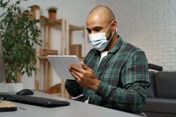 Injured Worker Wearing a Mask While Using a Tablet