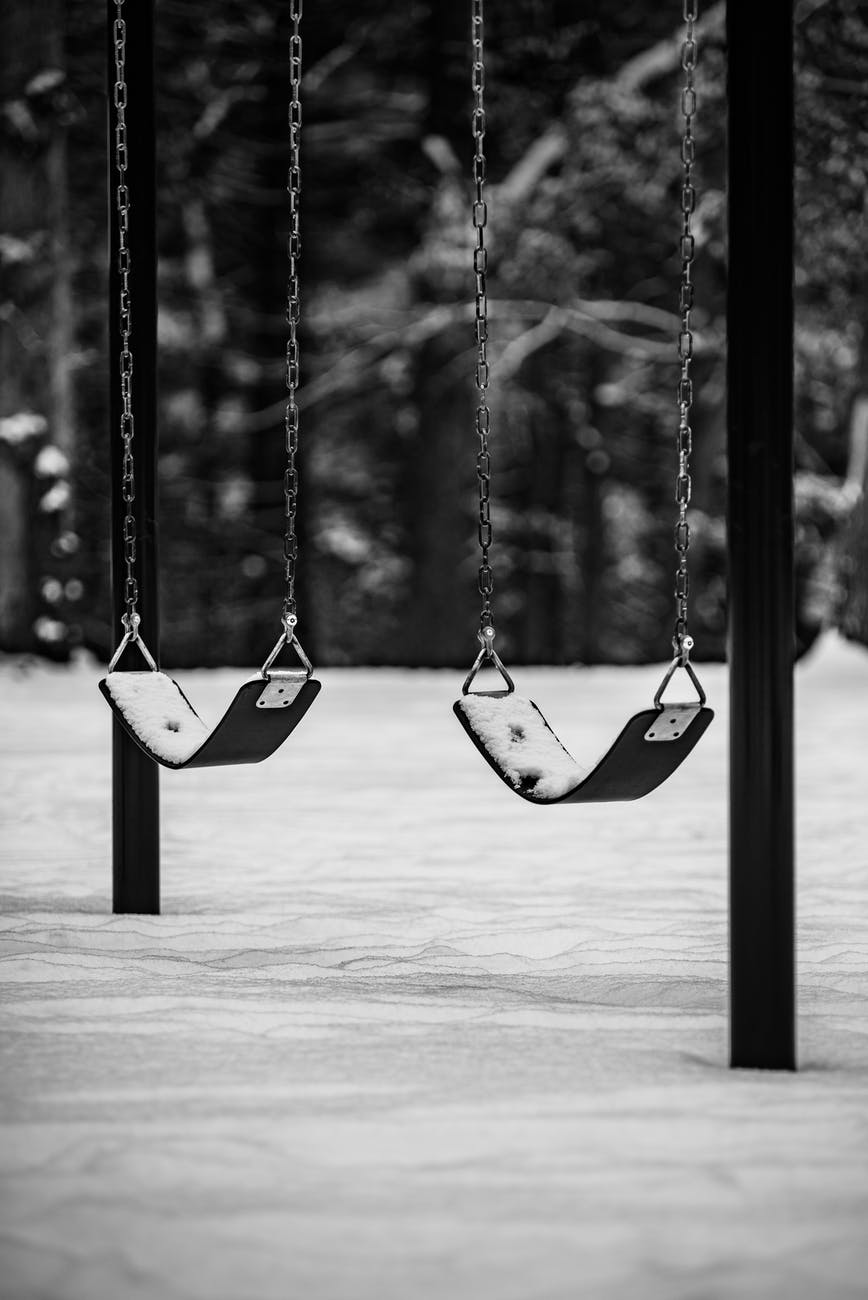 empty swingset on a playground in winter