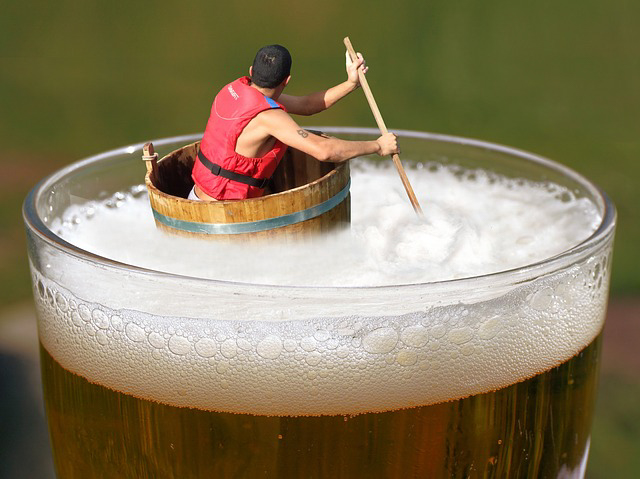 A man is in a barrel floating a massive glass of beer, the article is about the cost of DUIs in Florida