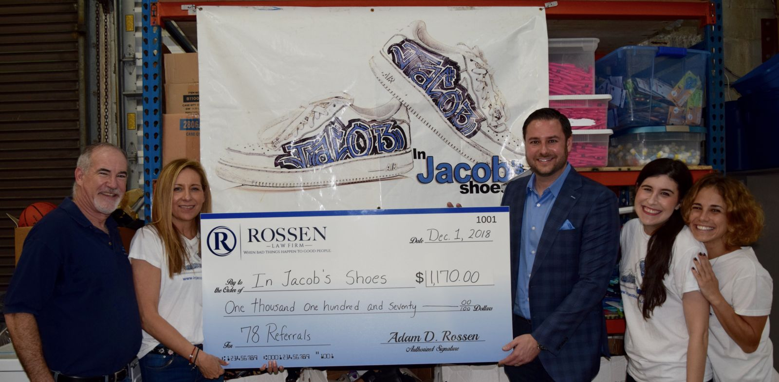 Adam stands with members of In Jacobs Shoes after donating 78 pairs of shoes to children in need in South Florida
