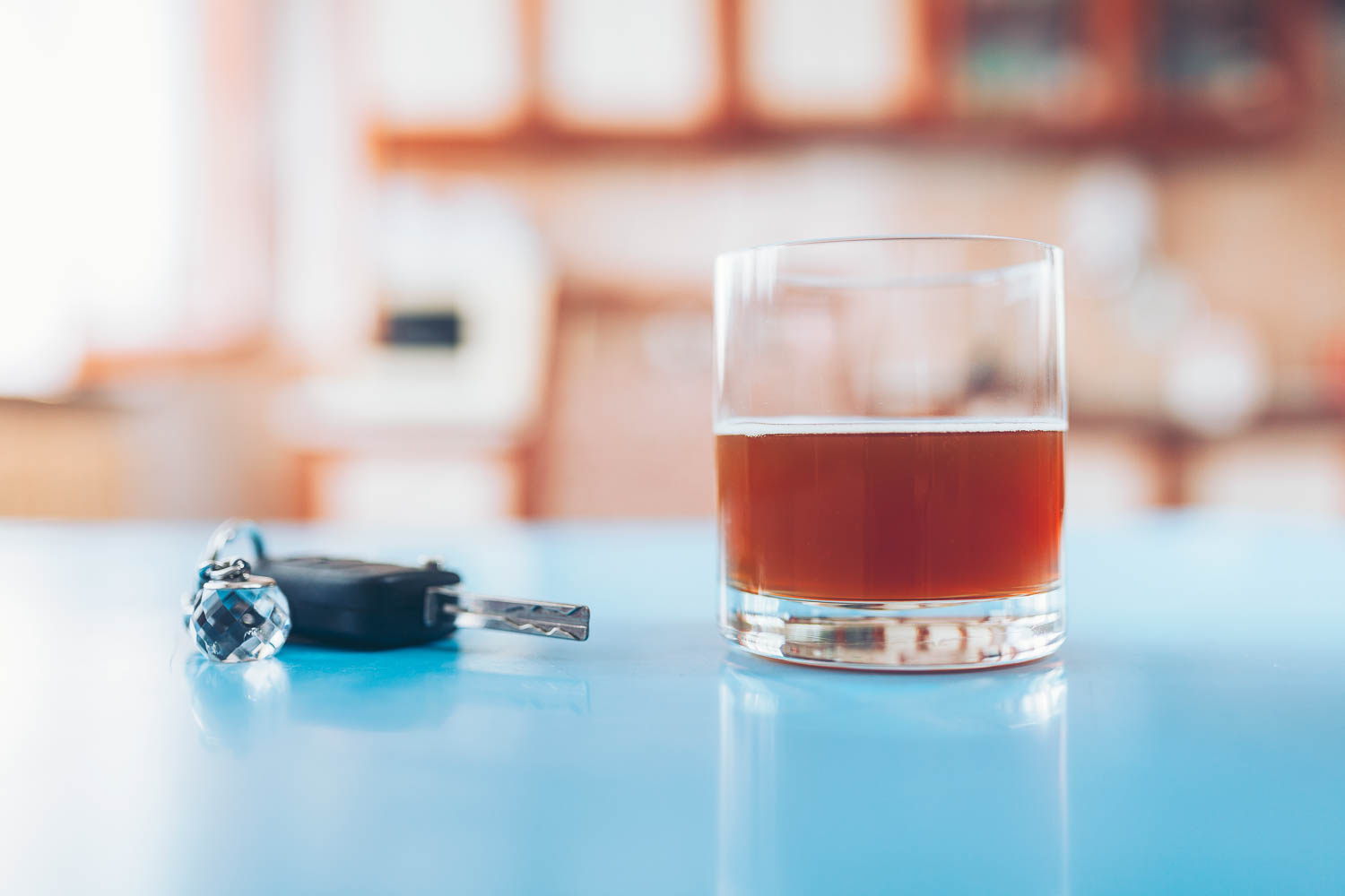 a glass of alcohol, maybe whisky, sits on the counter of a fort lauderdale, Florida, kitchen with a set of car keys