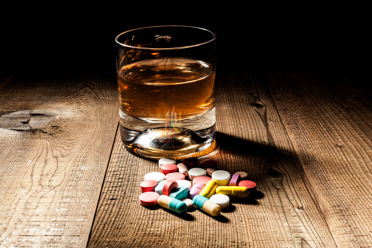 DUIs in Florida have to do with driving under the influence of alcohol or drugs - as pictured here with a glass of whiskey and pills on a wood table
