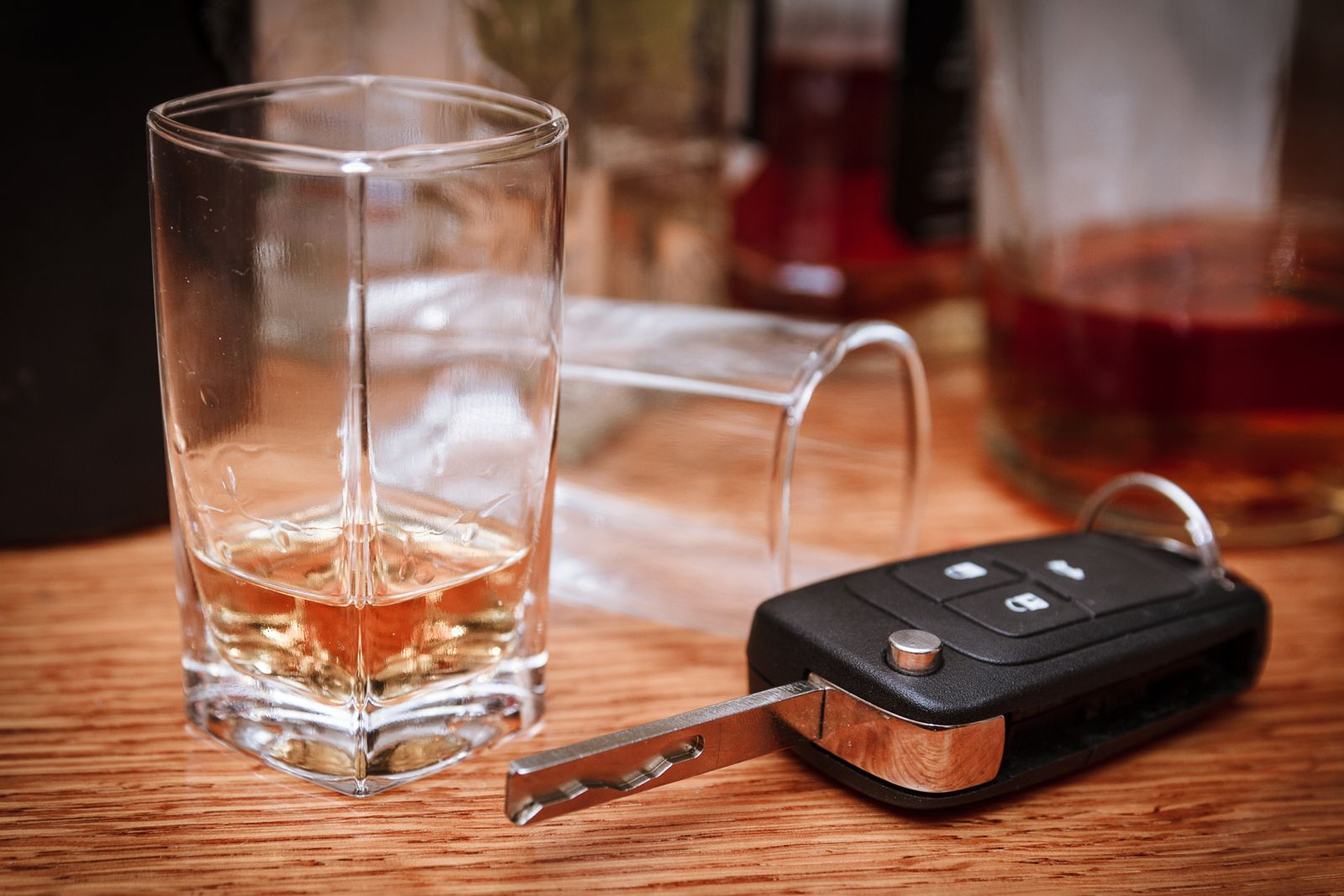 A glass of alcohol and keys sit on a table. If you've been arrested for drinking and driving you'll need a DUI lawyer