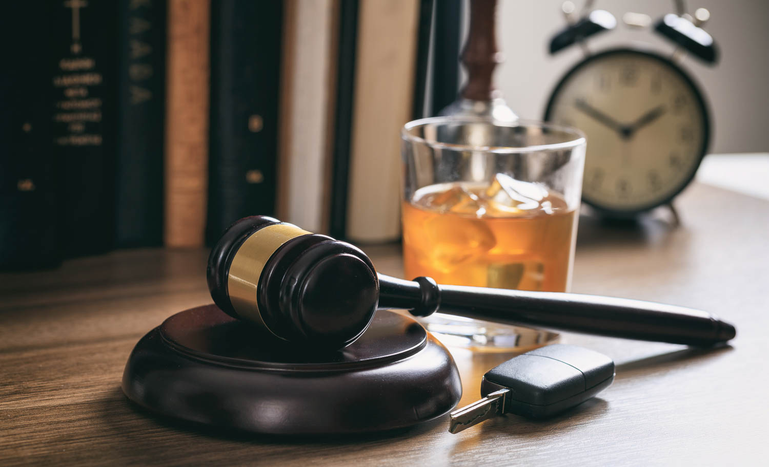A gavel sits on a desk in a Fort Lauderdale Court with a set of car keys and a glass of alcohol on the desk. The image is meant to depict a DUI charge in South Florida.