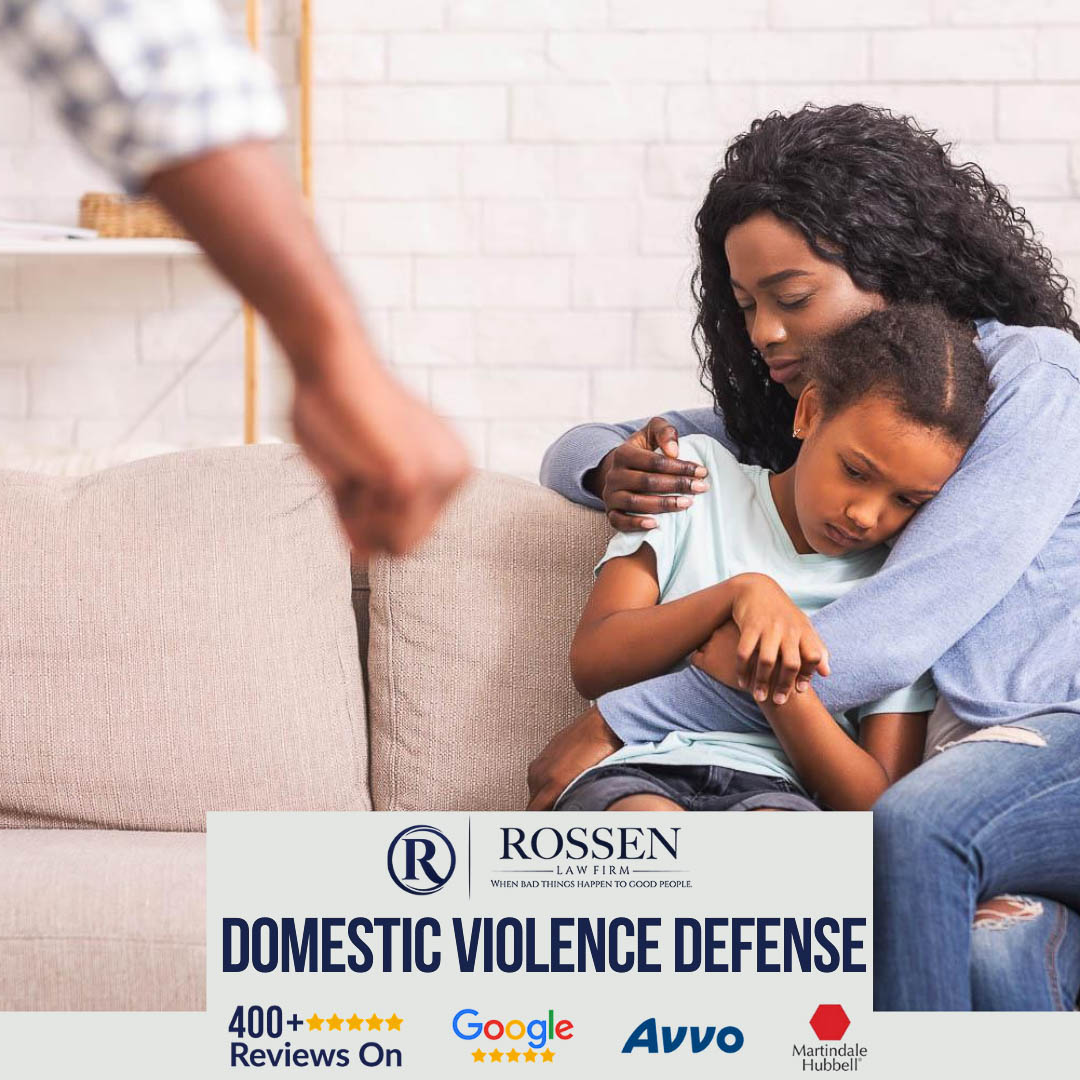 a mother holds a child on the couch in the photo while an angry man stands near them. the image explains in text that Rossen law Firm does Domestic Violence defense in Fort Lauderdale and south florida